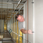 Installing hold down clips on the back of vertical ceiling tiles in a suspended ceiling drop
